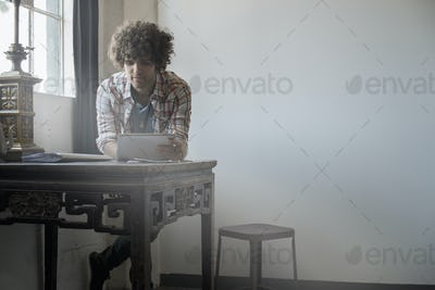 Loft living. A man sitting at a table by a window using a digital tablet.