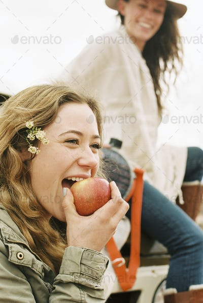 Two young women, one biting into an apple.