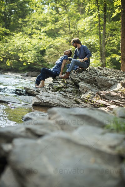 Two men seated in shade on the rocks by the river.