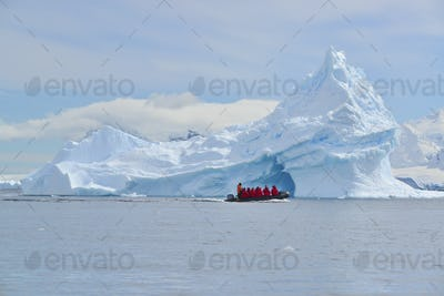 View of a group of people in a rubber boat near a towering iceberg in the Antarctic.