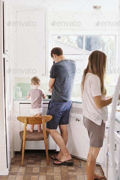 Couple standing in a kitchen, their son standing on a chair beside them.