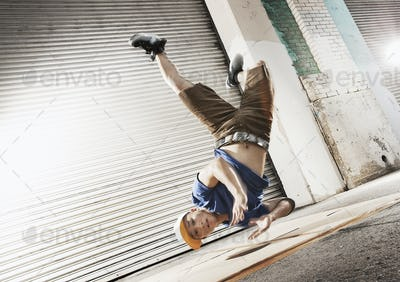 A young man upside down in mid air, break dancing doing a dive move on his shoulder.