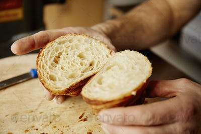 A man holding a croissant cut in half, to show the light layered texture of the cooked dough.