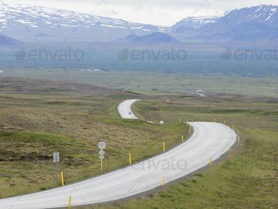 A winding mountain road through an open space.