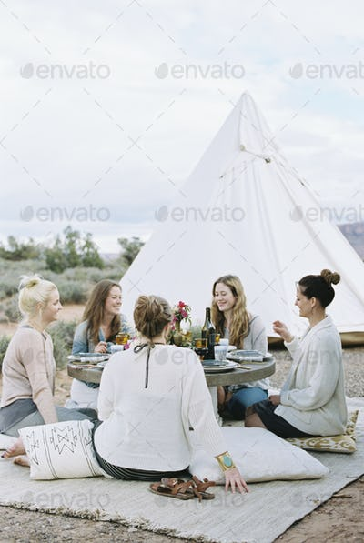 Group of women enjoying an outdoor meal by a teepee in the desert.