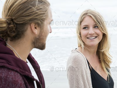 Young man and young woman on a beach, looking at each other, smiling.