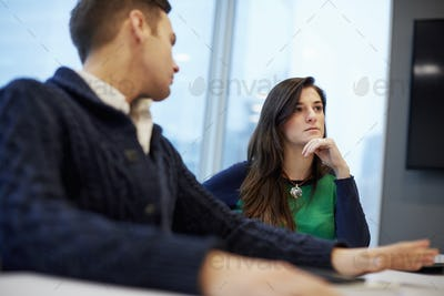 A man and woman seated at a meeting in an office.