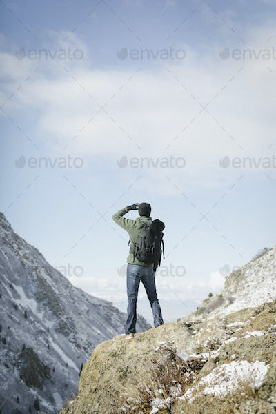 A man hiking in the mountains standing on an outcrop looking at the view.