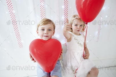 Young boy and girl posing for a picture in a photographers studio, holding red balloons.