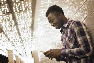 A man in a brightly lit space, a casino entrance, checking his smart phone.
