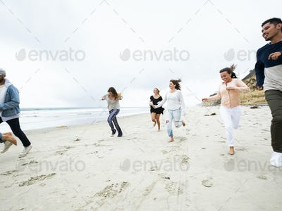 A group of young men and women running on a beach, having fun.