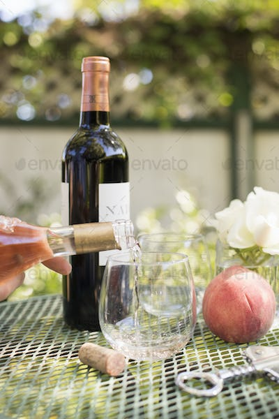 Rose wine being poured from a wine bottle into a glass.