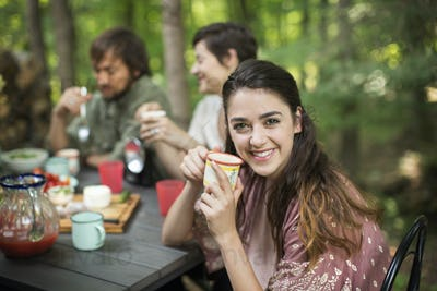 Three people seated around a table in a woodland clearing, one woman smiling at the camera.