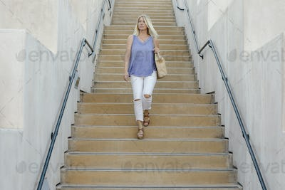 Blond woman walking down a staircase.