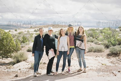 Group of five women, friends standing side by side in a desert landscape smiling.