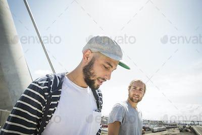 Two young men walking along a bridge.
