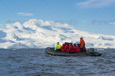 Group of people sailing in a boat, snow-covered Antarctic mountains in the background.