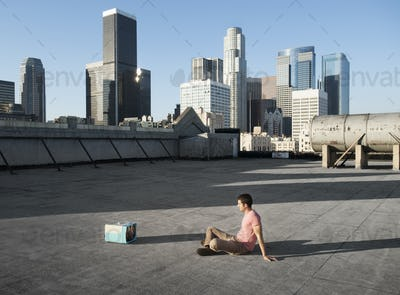 A man sitting on a city rooftop watching a small blue portable television.