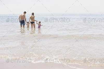 Couple with their son and daughter, A family standing in shallow water off the beach.