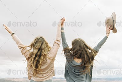 Rear view of two women standing side by side, holding hands, with their arms raised up in the air.