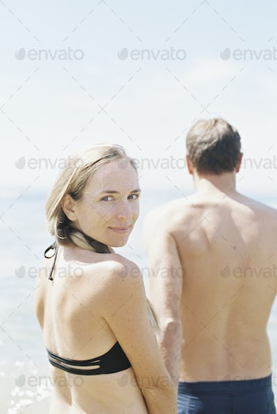 Couple in swimwear by the ocean, woman smiling at camera.