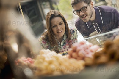 A couple looking at the window display in a confectionery shop.