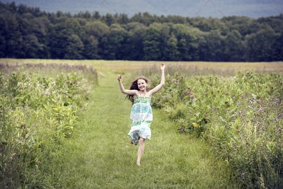 A girl running through a meadowwith her arms above her head.