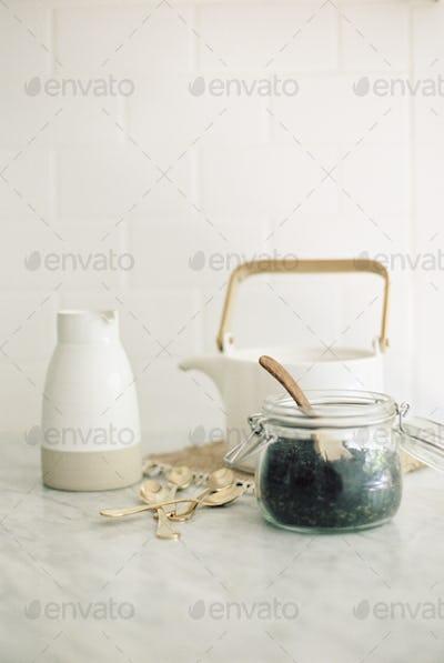 Tea pot, jug and a glass jar with black tea leaves.
