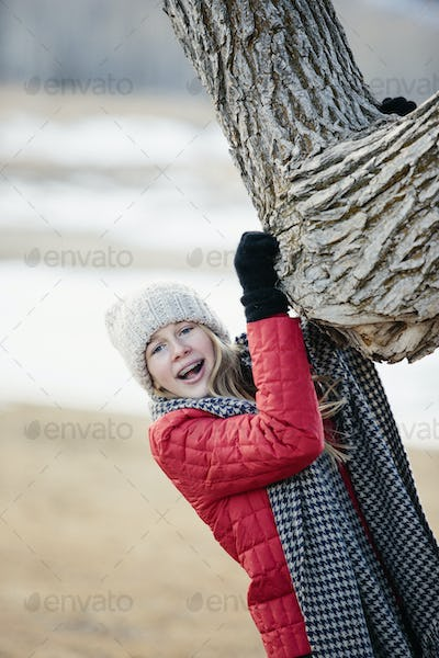 A young girl in a red jacket, and long scarf, gripping a tree trunk.