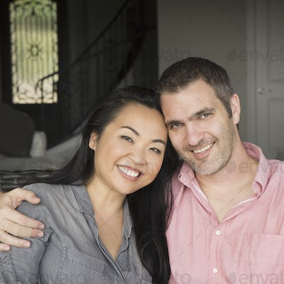Smiling man and woman sitting on a sofa, hugging, and looking at the camera.