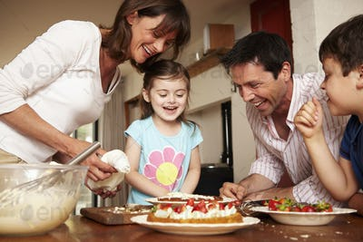 A family, two parents and two children in the kitchen icing a cake with fruit and cream.