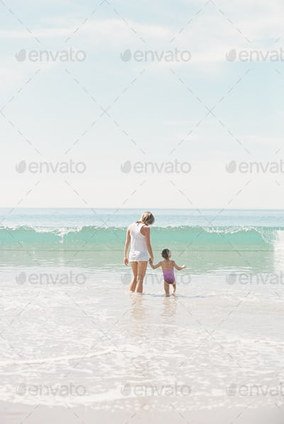 Woman standing hand in hand with her daughter on a sandy beach watching a wave.