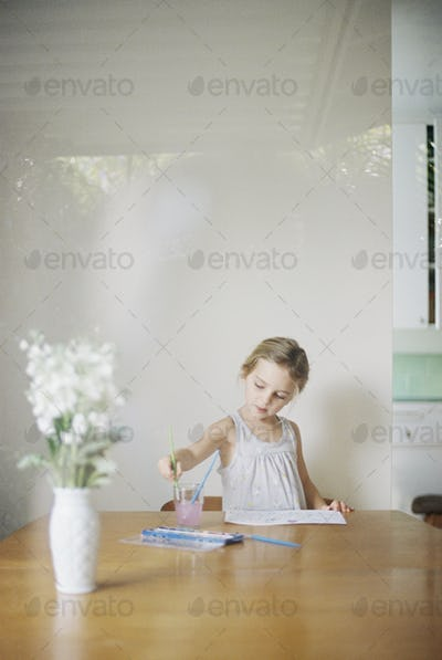 Young girl sitting at at a table, painting, a vase with white flowers.