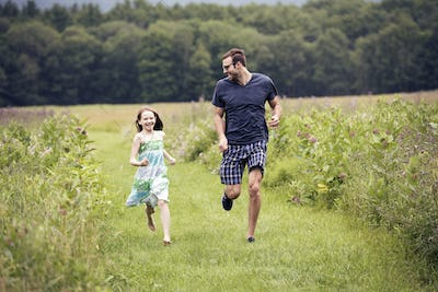 A man and a young child running through a wildflower meadow.
