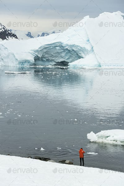 Man standing on the snow-covered shore in Antarctica, icebergs and mountains in the background.