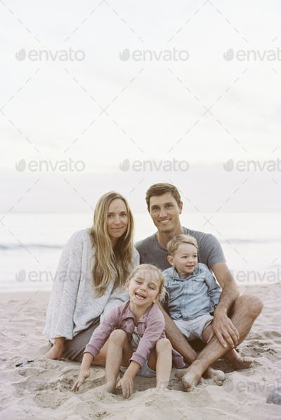 Couple sitting with their son and daughter on a sandy beach by the ocean, looking at camera.