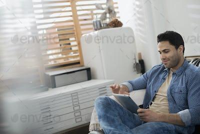 A man sitting using a digital tablet.