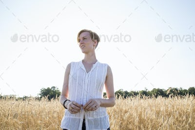 Half length portrait of a young woman standing in a cornfield.