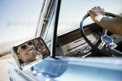 View in the wing mirror of the driver of a blue convertible and his companion