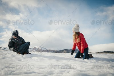 A brother and sister playing in the snow.