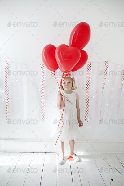 Young girl posing for a picture in a photographers studio, holding red balloons.