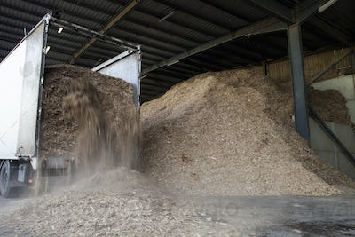 Stored organic waste being poured from a lorry into a large warehouse for biomass fuel production.