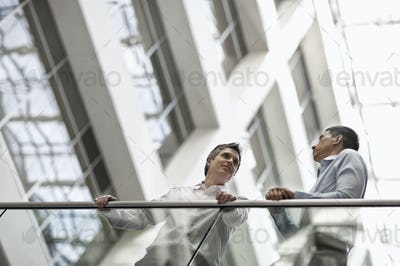 Two men, business colleagues, standing by a railing in an atrium or courtyard, talking.
