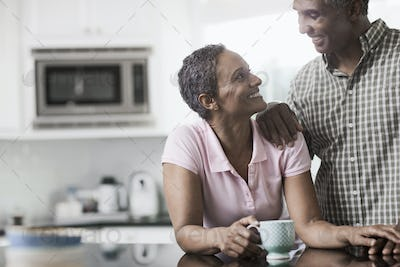 A couple in the kitchen of their home, smiling at each other.