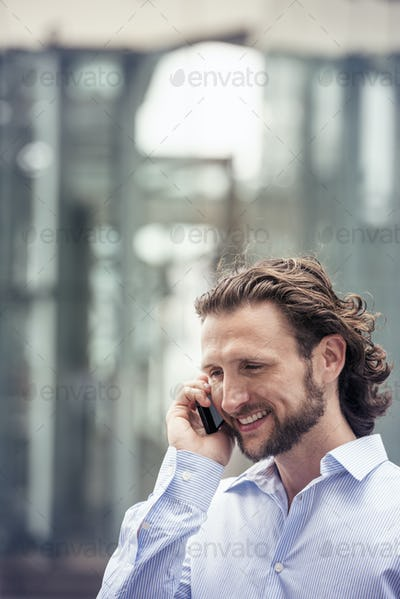 A man with a beard talking on a cell phone on a street in the city.