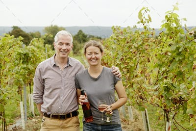 A couple, vineyard founder and her partner standing among the rows of vines.