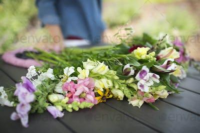 A bunch of summer garden flowers on an outdoor table.