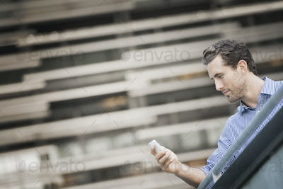 A man standing on a street checking his smart phone.