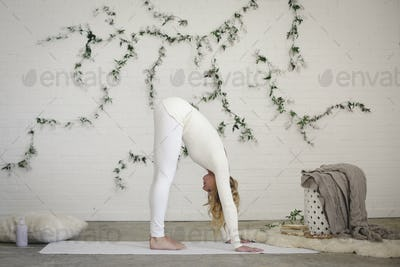 A blonde woman  bending forward to the floor, stretching her back with her hands down on the floor.