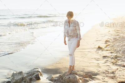 Woman walking along a sandy beach by the ocean.